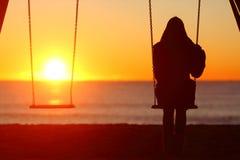 Sola mujer que se sienta en un oscilación que comtempla puesta del sol imágenes de archivo libres de regalías
