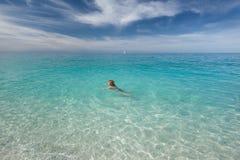 Sola natación de la mujer en el mar transparente en el día idílico fotografía de archivo