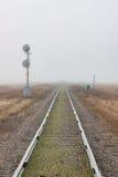 Sola pista de ferrocarril que retrocede en la niebla imágenes de archivo libres de regalías