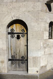 Sola puerta de madera en pared vieja con los elementos forjados Foto de archivo libre de regalías