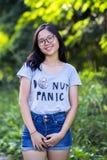 Sola señora asiática enérgica de moda joven con las gafas largas del pelo que llevan la mezclilla corta del dril de algodón en el Fotografía de archivo libre de regalías