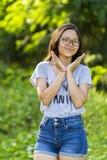 Sola señora asiática enérgica de moda joven con las gafas largas del pelo que llevan la mezclilla corta del dril de algodón en el Imagen de archivo