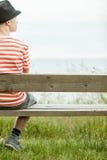 Sola sentada adolescente en el lado del banco Fotografía de archivo libre de regalías