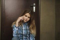 Sola tenencia adolescente triste un teléfono móvil Fotografía de archivo