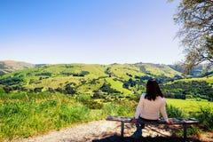 Solamente la muchacha se sienta en banco que admira paisaje en Akaroa, Nueva Zelanda Éste es fotos de archivo libres de regalías