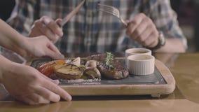 Solamente manos: hombre en filete que espera del restaurante de la parrilla