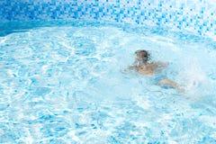 Solamente muchacho irreconocible del niño que se ahoga en la piscina foto de archivo