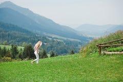 Solamente mujer que camina en un prado - pensativo imagen de archivo