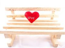 Solamente pequeña almohada roja con palabra del amor en silla de madera vacía beige Fotografía de archivo