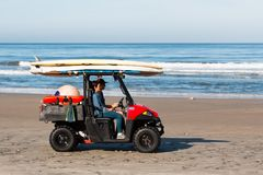 Lifeguard Personnel on Solana Beach in Rescue Vehicle. SOLANA BEACH, CALIFORNIA/USA - APRIL 22, 2018: Lifeguard personnel transport surfboards and other stock images