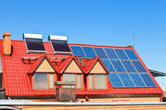 Solar Batteries and heaters on home roof. Contemporary energy-saving technology - Solar Batteries and heaters on home roof royalty free stock photos