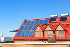 Solar Batteries and heaters on house roof Royalty Free Stock Photography
