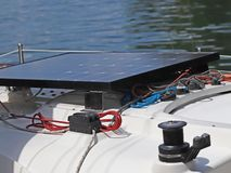 Solar battery for the development of electric current under the influence of sunlight mounted on the deck of a small sailing yacht stock photos