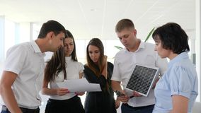 Solar battery Into hands of businessman with colleagues in modern office. Space
