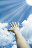 Solar beams. The stretched hand with the sky between solar beams Stock Photos