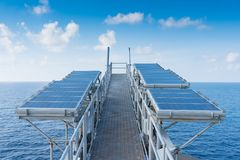 Solar cells at flare bridge at offshore oil and gas wellhead remote platform for charging battery of electrical and control system. On platform, Power and royalty free stock photos