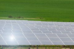 Solar cells. Photovoltaic (PV) solar cells with sunlight reflection in green field royalty free stock photos