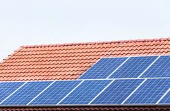 Solar cells or photovoltaics installing on red concrete tiles roof house turn up skyward absorb the sunlight from the sun. Close up rows array of polycrystalline stock images