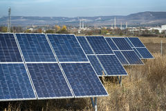 Solar cells plant in filed. In front of small town and factory Royalty Free Stock Photography