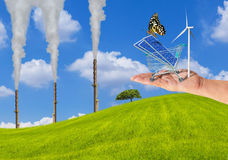 Solar cells in shopping trolley cart with butterfly and wind turbine on hand and coal power plant chimney with smoke on grass hill Royalty Free Stock Images