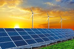 Solar panels and wind turbines at sunset. Stock Photo
