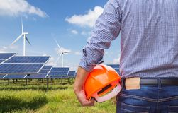 Solar cells with wind turbines generating electricity in power station on blue sky background. Alternative renewable energy from nature Ecology concept royalty free stock photography