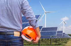 Solar cells with wind turbines generating electricity in power station on blue sky background. Alternative renewable energy from nature Ecology concept stock photo