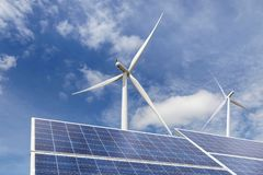 Solar cells with wind turbines in hybrid power plant systems station on blue sky background Stock Images