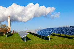 Solar collectors, fossil-fuel power station and wind turbines in Stock Images