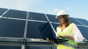 Solar construction and a young female worker walking along it with a laptop. Green energy concept. stock video footage