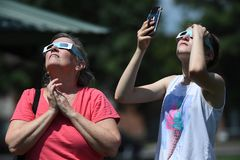 Solar Eclipse of August 21, 2017. Marion, IL, USA – August 21, 2017: A man looks into the sun using solar eclipse glasses in Marion, Illinois stock images