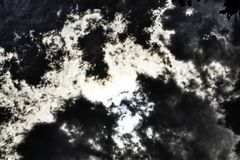 Solar Eclipse Behind Dramatic Sky. Clouds accenting eclipsing sun on stormy day royalty free stock photo