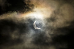 Solar eclipse in cloudy sky Stock Images