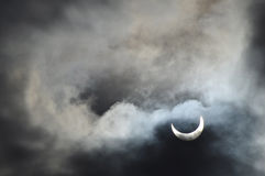 Solar eclipse. Partial solar eclipse with the clouds being lit by the sun Royalty Free Stock Images