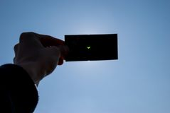 Solar eclipse in Poland. CRACOW, POLAND - MARCH 20, 2015: An observer watching a partial solar eclipse throught the dark glass in southern Poland Stock Photography