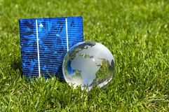 Solar energy cells with glas globe and miniature house in green grass stock photo
