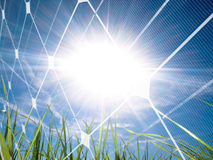Solar energy concept. Beautiful grass field at spring against the sun with photovoltaic panel Royalty Free Stock Photo
