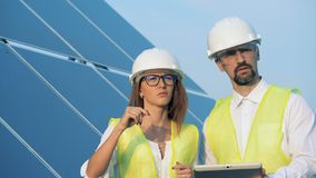 Solar energy concept. Solar array and two specialists walking along it while having a discussion. Solar array and two specialists walking along it while having a stock video