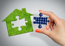 Solar energy concept, green puzzle house with solar battery wind stock photos