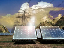 Solar Energy and electrical net. Solar panels producing energy to electric pillars being a part of a network, through fields and mountains Royalty Free Stock Images