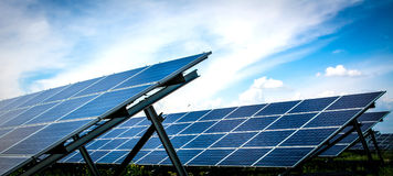 Solar Energy Panel. S in the middle of the field with bright blue sky above Stock Photos