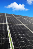 Solar energy panels against blue sky with clouds. Stock Photo