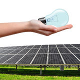 Solar energy panels and bulb in hand Royalty Free Stock Photography