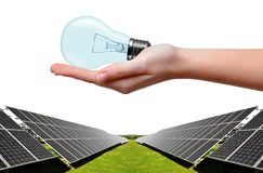 Solar energy panels and bulb in hand Stock Images