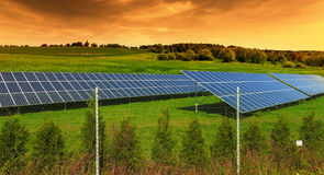 Solar energy panels on green field, sunset sky Stock Photo