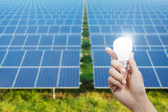 Solar energy panels and Light bulb in hand, energy Royalty Free Stock Photos