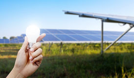 Solar energy panels and Light bulb in hand, energy. Solar energy panels and Light bulb in hand, Green energy concept Stock Image