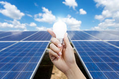 Solar energy panels and Light bulb in hand, energy royalty free stock images