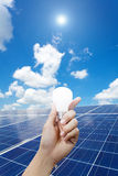 Solar energy panels and Light bulb in hand, energy Stock Photos
