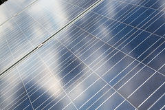 Solar energy panels with reflections of cloudy sky Stock Photos